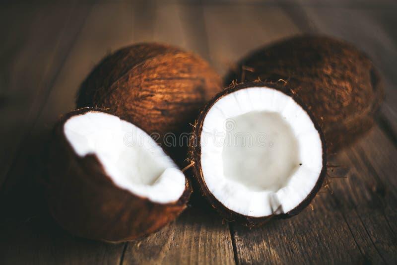 La mitad madura cortó el coco en un fondo de madera La mitad madura cortó el coco en un fondo de madera Crema y aceite del coco foto de archivo libre de regalías