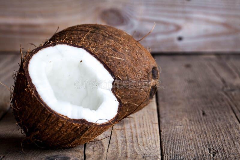 La mitad madura cortó el coco en un fondo de madera La mitad madura cortó el coco en un fondo de madera Crema y aceite del coco imágenes de archivo libres de regalías