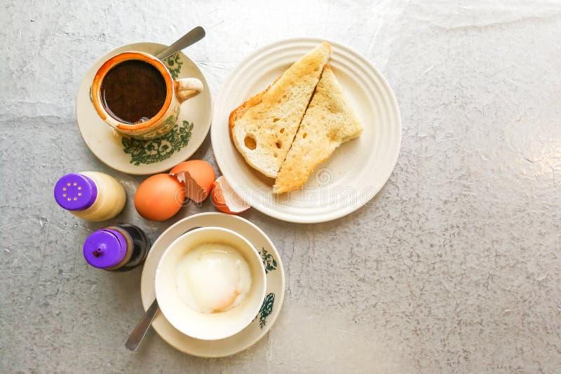 La mitad tradicional asiática del desayuno hirvió los huevos, el pan de la tostada y el co fotografía de archivo