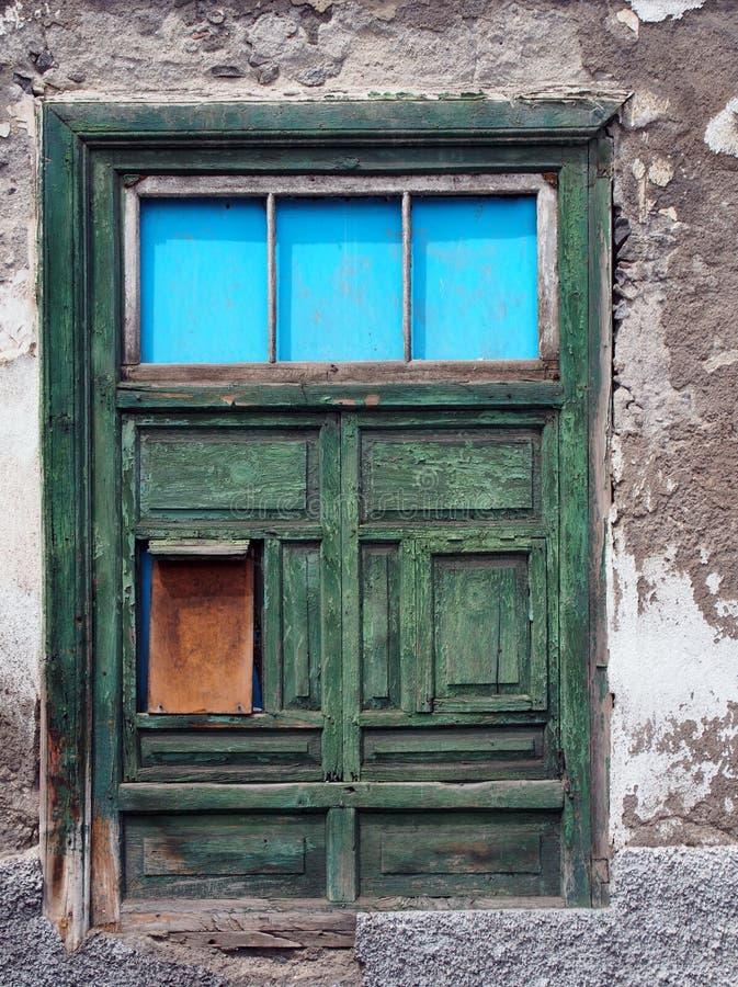 La mitad verde shuttered la ventana lamentable vieja en una casa de decaimiento imágenes de archivo libres de regalías