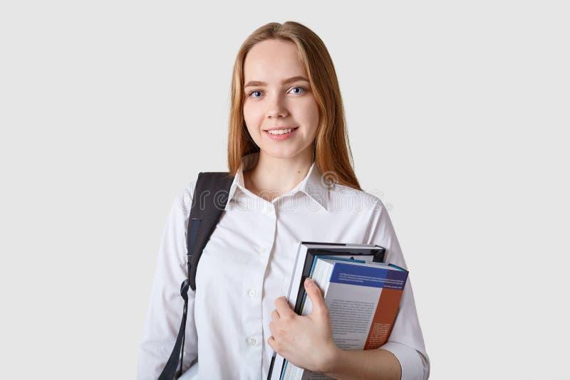 La mochila ascendente cercana de los teenagercarries de la chica joven del portraitof, sostiene la carpeta colorida con los papel fotos de archivo libres de regalías