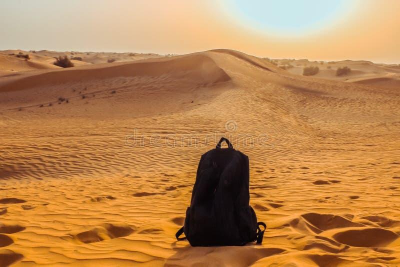 La mochila negra entre el desierto de Dubai En mayo de 2019 foto de archivo libre de regalías
