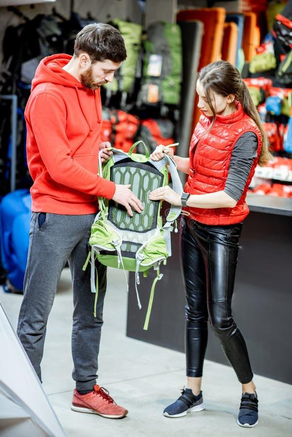 La mochila que intenta de la mujer con el hombre en los deportes hace compras fotografía de archivo libre de regalías