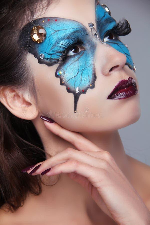 La moda compone. Maquillaje de la mariposa en mujer hermosa de la cara. Arte P fotos de archivo libres de regalías