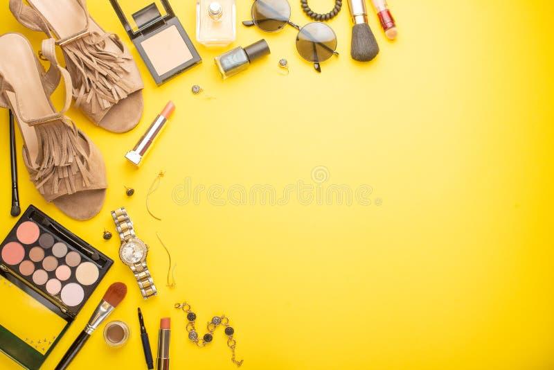 La moda de las mujeres, y belleza Los accesorios y los cosm?ticos de las mujeres en un fondo amarillo bandera fotos de archivo libres de regalías