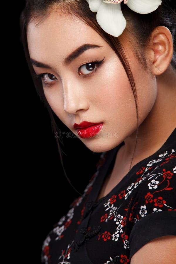 La moda del estudio tiró de mujer asiática con la flor blanca en pelo fotografía de archivo