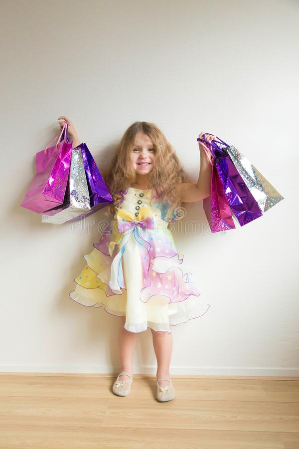 La moda embroma compras Niña sonriente hermosa fotos de archivo