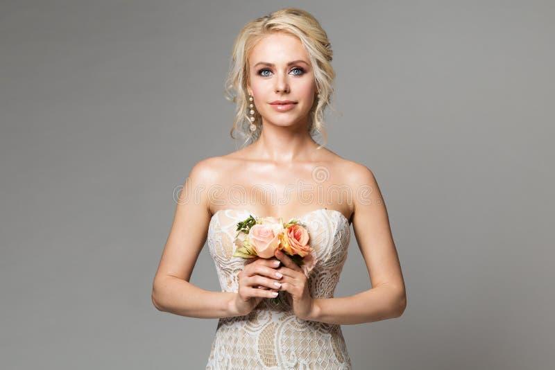 La moda modela el retrato de la belleza con el ramo de las flores, el maquillaje hermoso y el peinado, tiro de la mujer del estud imagen de archivo