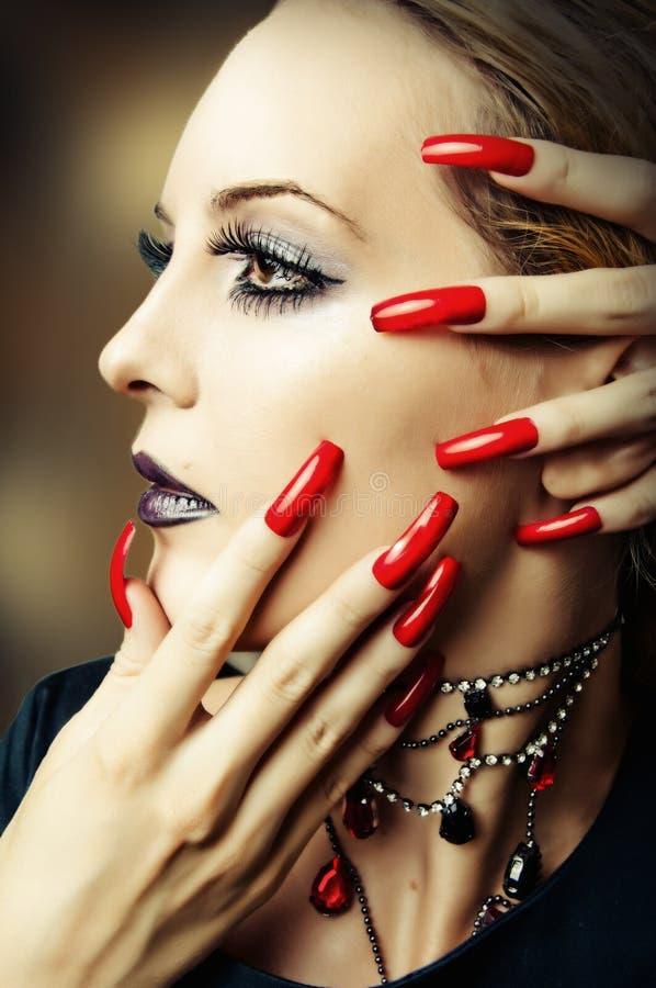 La mode composent et de longs clous rouges photo stock