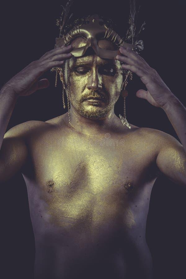 La mode, homme avec le corps a peint le masque de plume d'or et l'épée d'acier photos libres de droits