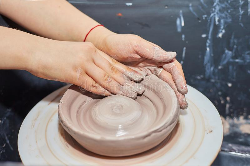 La modellistica dell'argilla su un ` s del vasaio spinge dentro l'officina delle terraglie immagine stock