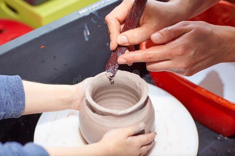 La modellistica dell'argilla su un ` s del vasaio spinge dentro l'officina delle terraglie fotografia stock