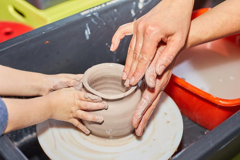 La modellistica dell'argilla su un ` s del vasaio spinge dentro l'officina delle terraglie immagini stock