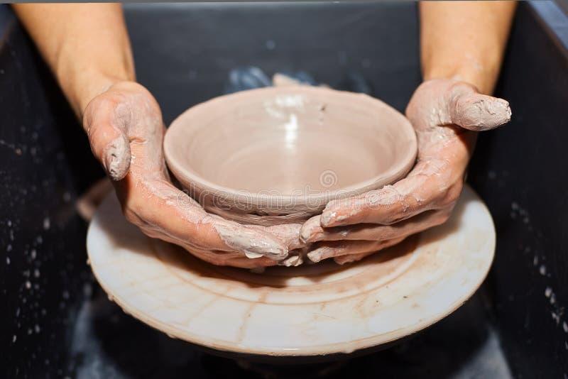 La modellistica dell'argilla su un ` s del vasaio spinge dentro l'officina delle terraglie immagini stock libere da diritti