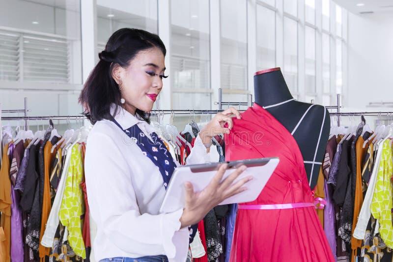 La modista de sexo femenino trabaja con la tableta en el boutique fotografía de archivo