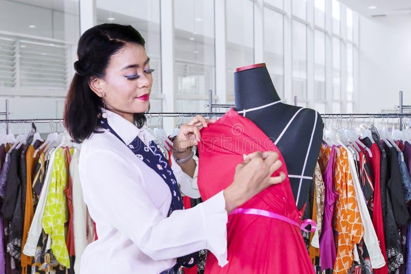 La modista joven ajusta el vestido rojo en un maniquí fotos de archivo