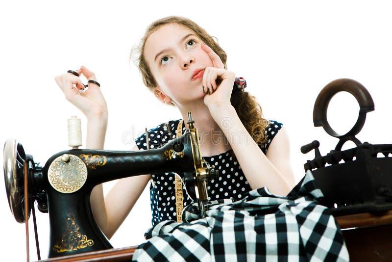 La modista Teenaged de la muchacha piensa y el plan utilizará antes la máquina de coser manual foto de archivo