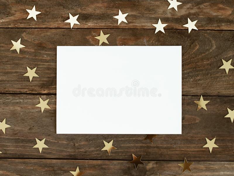 La mofa encima de la tarjeta del greeteng en el fondo rústico de madera con oro de la Navidad protagoniza confeti Invitación, pap foto de archivo