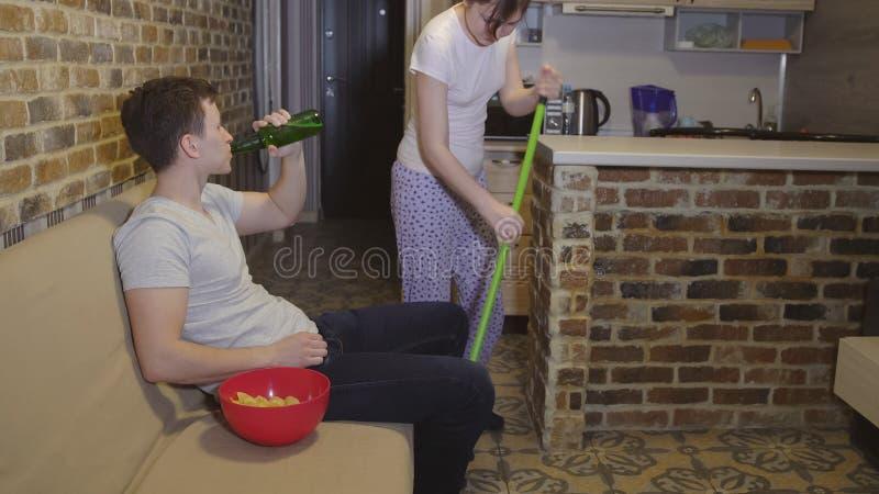 La moglie fa la pulizia, impedente il marito per guardare il calcio immagine stock libera da diritti