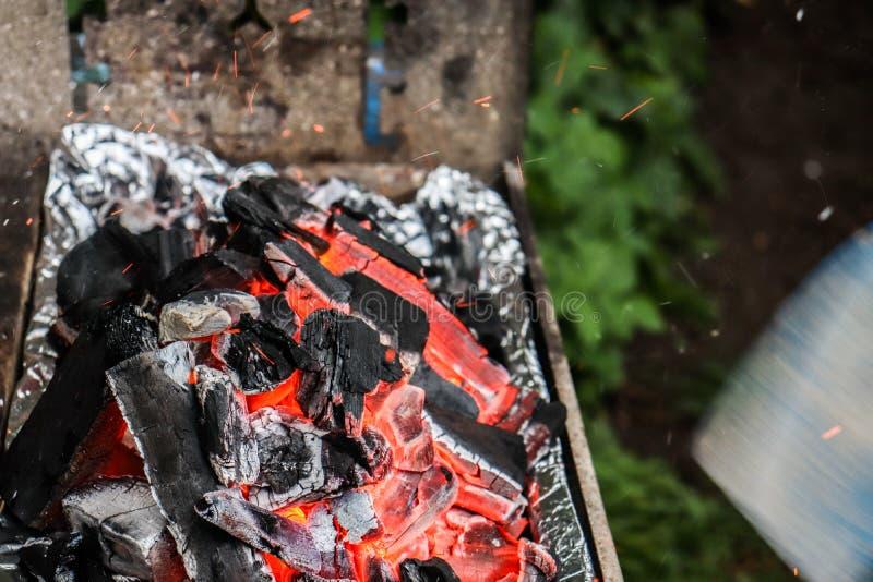La moitié a brûlé le charbon avec des étincelles volant autour photo stock