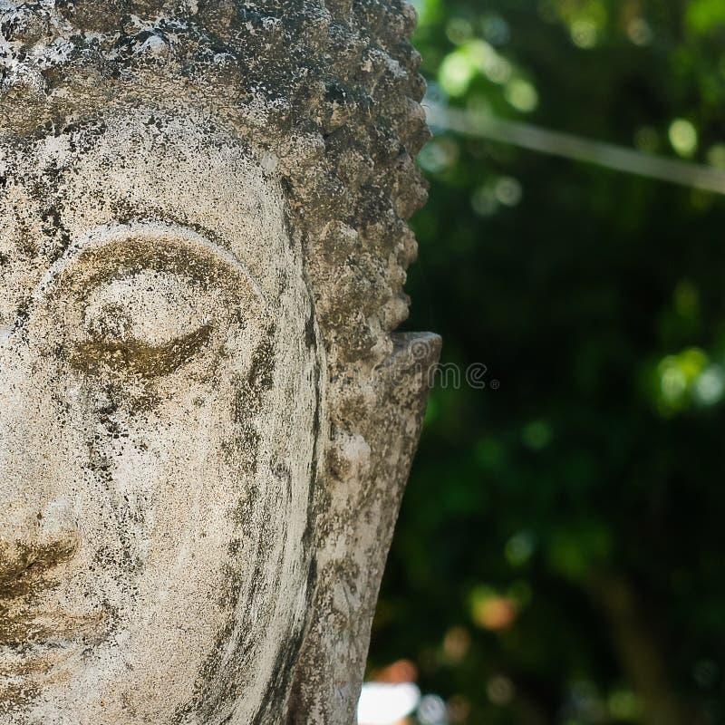 La moitié de vieux Bouddha en pierre font face images stock