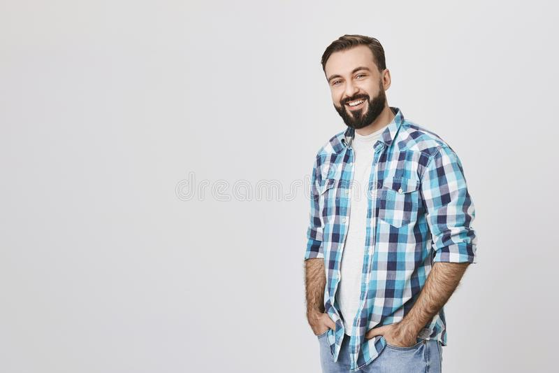 La moitié debout de type agréable barbu adulte a tourné avec des mains dans des jeans, souriant heureusement sur le fond gris bea photo stock