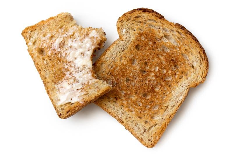 La moitié mangée a beurré la tranche de pain grillé de blé entier et de sli sec entier image stock