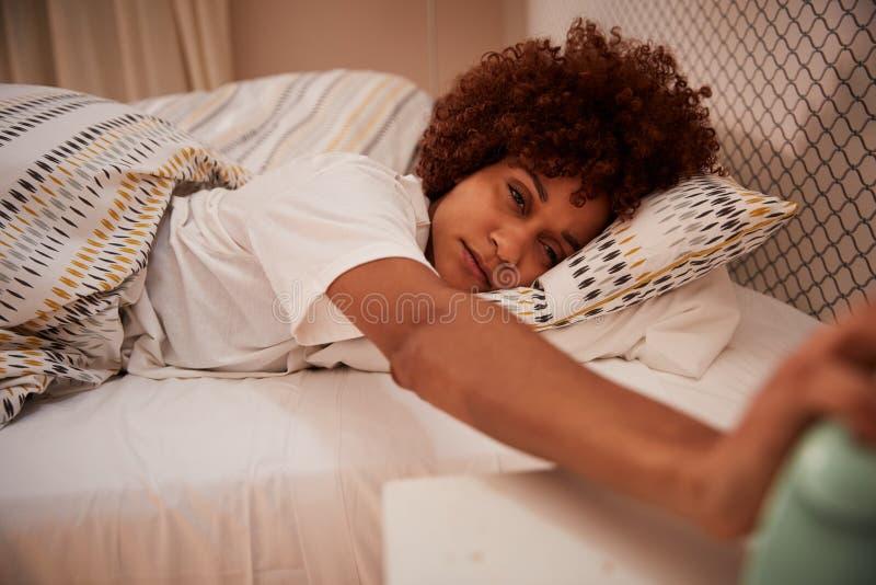 La moitié millénaire de femme d'Afro-américain endormie dans le lit, atteignant pour arrêter le réveil, se ferment  photos libres de droits
