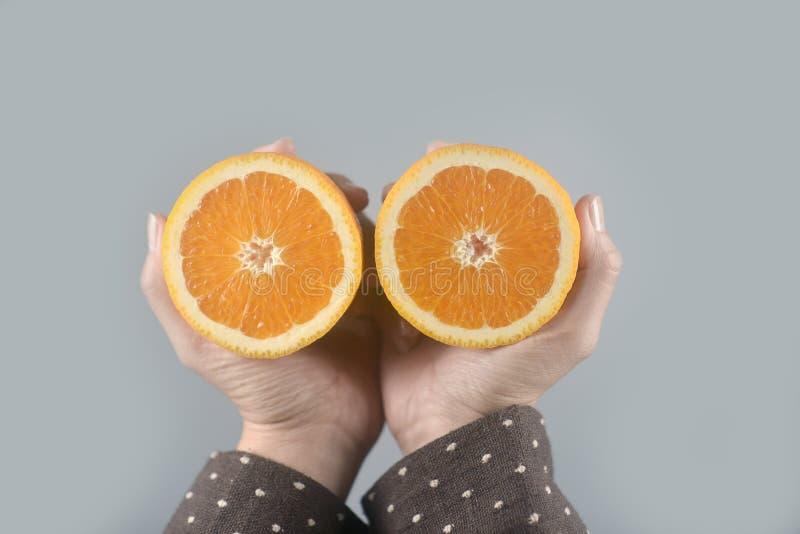 La moitié orange a coupé 2 morceaux sur des mains de femmes avec le manteau brun sur le fond gris-clair Image horizontale photo libre de droits