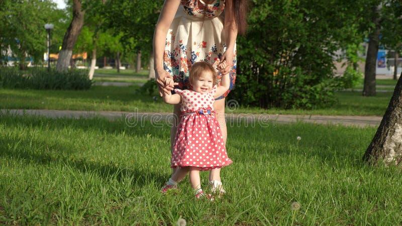 La momia camina en parque en césped con el pequeño niño, mamá enseña para caminar a poca hija, niño lleva a cabo la mano de su ma imagen de archivo libre de regalías