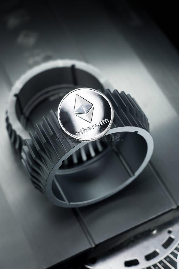 La moneda crypto de plata de Ethereum miente en la rueda dentada imagen de archivo