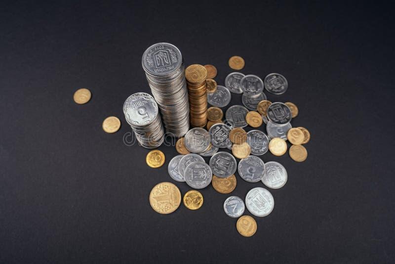 La moneda de ahorro del dinero apila hryvnia ucraniano del fondo oscuro de la torre imagen de archivo