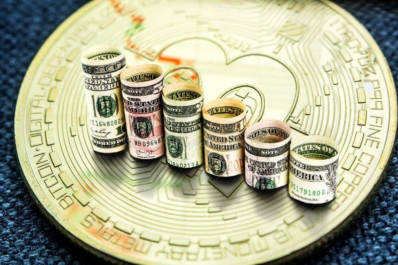 La moneda de oro del bitcoin con los dólares que forman caer camina foto de archivo