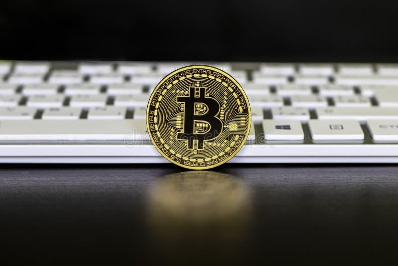 La moneda de oro de los soportes del bitcoin en el fondo negro delante de los teclados blancos fotografía de archivo