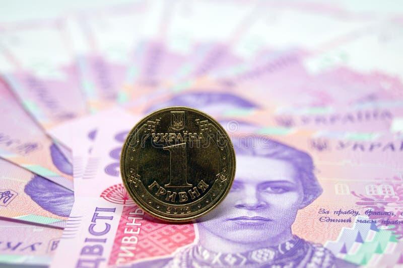 La moneda es un hryvnia contra la perspectiva del billete de banco de papel fotografía de archivo