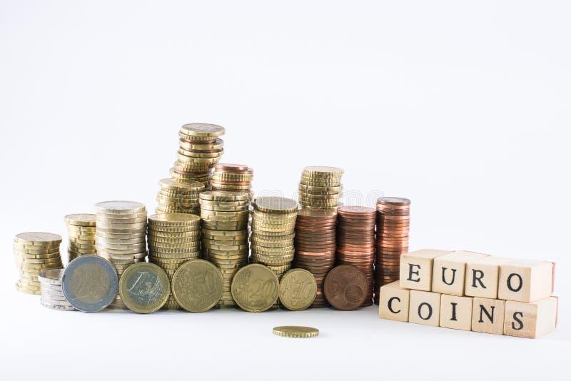 La moneda euro acuña las escalas del edificio y los cubos de madera que forman las monedas del euro de las palabras imagen de archivo libre de regalías
