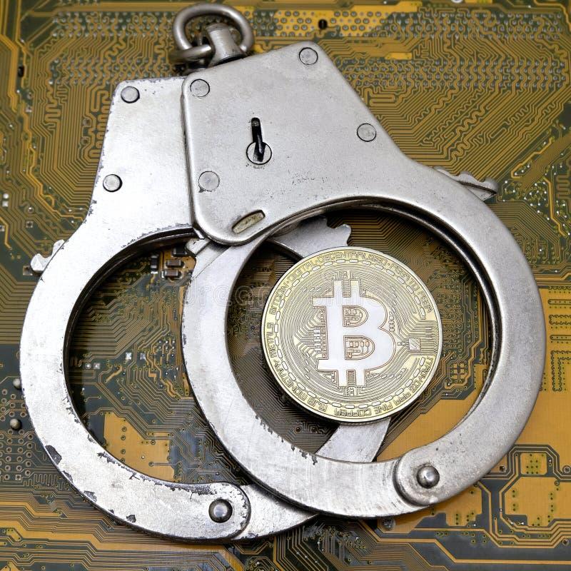 La moneda real del bitcoin miente en las esposas de acero cerradas contra el tablero de electrónica amarillo del ordenador Una im imagen de archivo