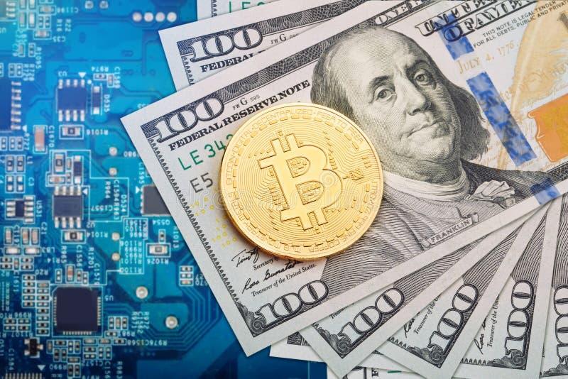 La moneta di bitcoin si trova sui dollari contro lo sfondo della scheda video fotografia stock
