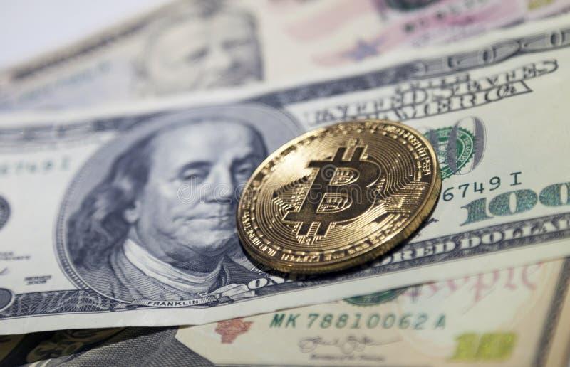 La moneta dorata del bitcoin sui dollari americani si chiude su immagini stock libere da diritti
