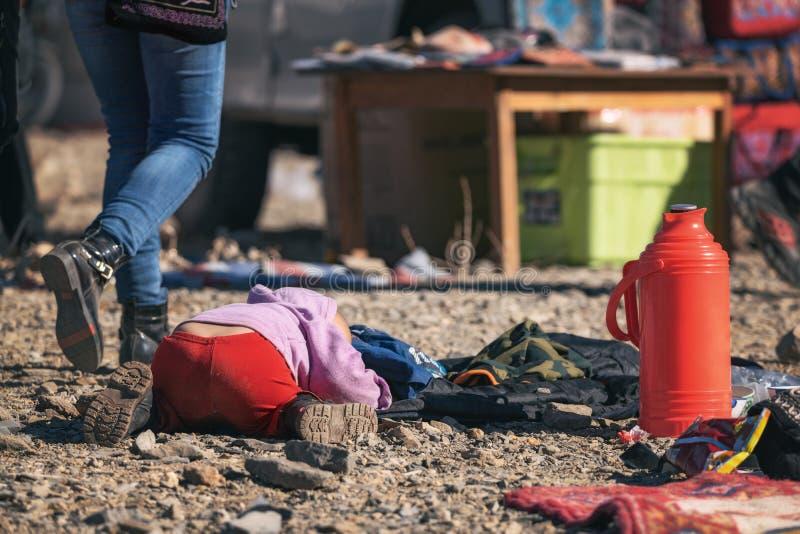 La Mongolia incontaminata Ragazzo mongolo in pantaloni rossi che dorme sulle pietre fra passare la gente durante l'Eagle Hunters  fotografia stock libera da diritti