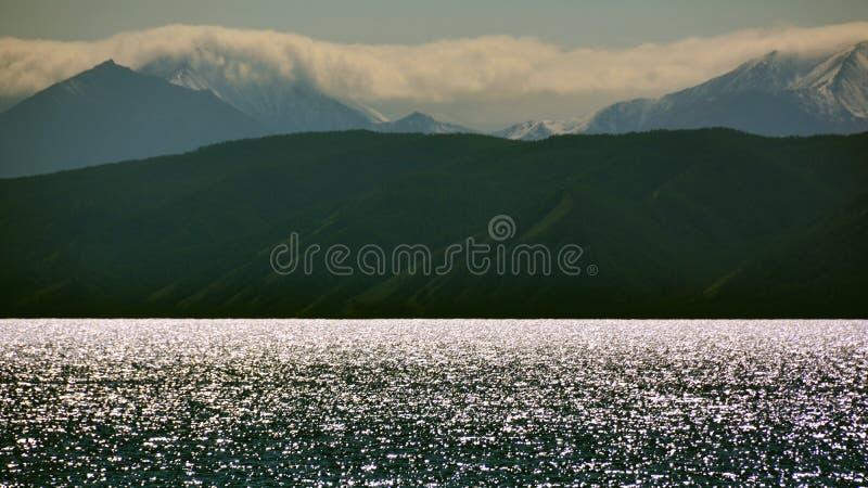 La Mongolie la soirée sur le rivage de l'horizon argenté d'étincelles de Hovsgol de lac, montagnes de Sayan la première neige pen images stock