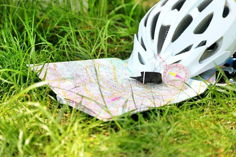 La montaña biking, mapa, compás del casco está en la hierba foto de archivo