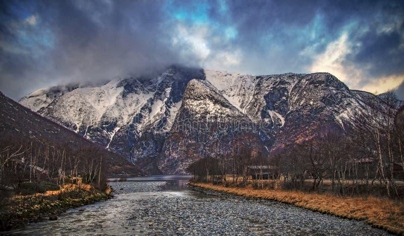 La montaña casi púrpura con nieve sube fuera del fiordo como una pared de piedra debajo de un cielo azul y dramático fotografía de archivo libre de regalías