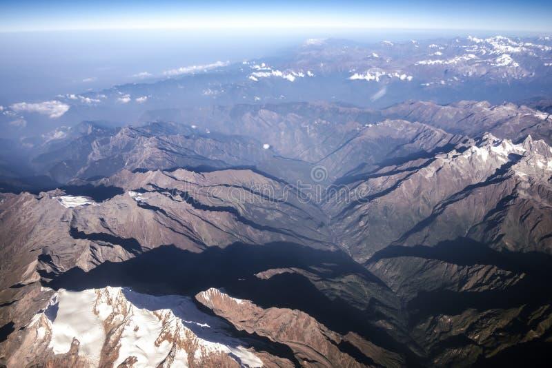 La montaña de Himalaya y el cielo azul de la ventana del aeroplano imagen de archivo