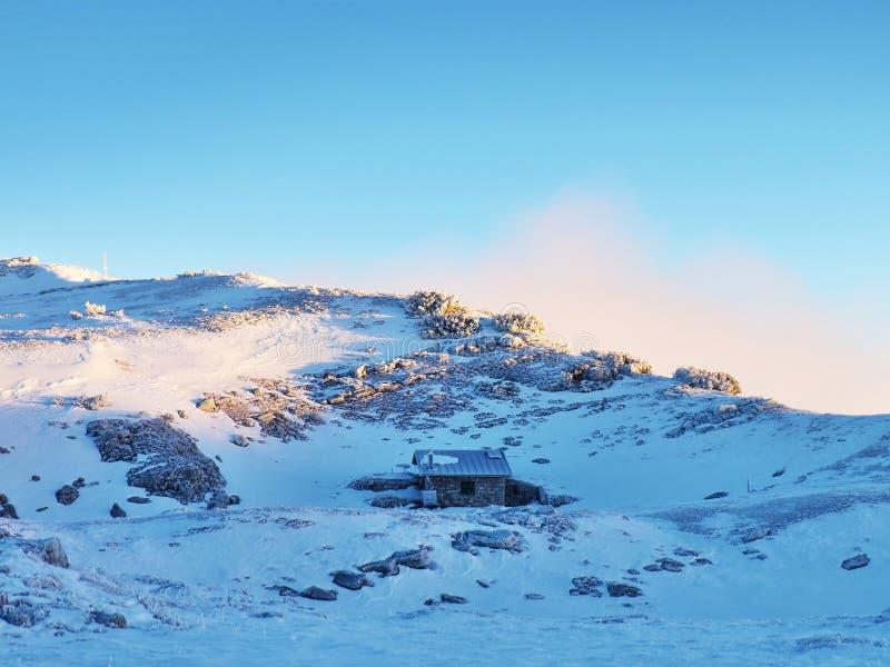 La montaña del invierno Nevado y la cabaña pedregosa vieja en pequeño valle gritan el pico Cielo azul claro fotos de archivo libres de regalías