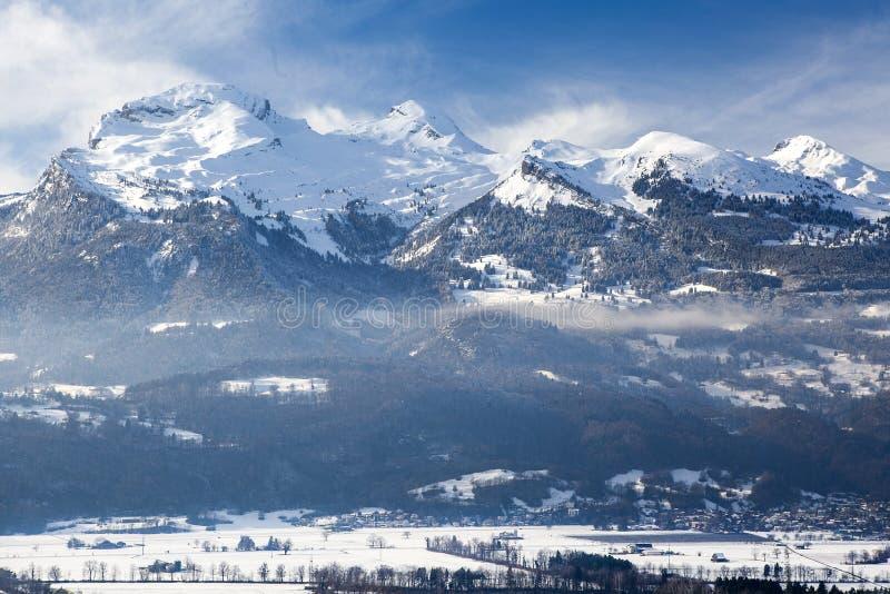 La montaña en la nieve y una ciudad en las montañas en invierno fotografía de archivo