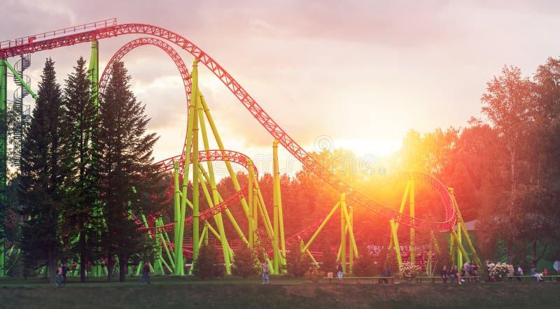 La montaña rusa en los atractions centrales parquea en el tiempo de la tarde fotos de archivo
