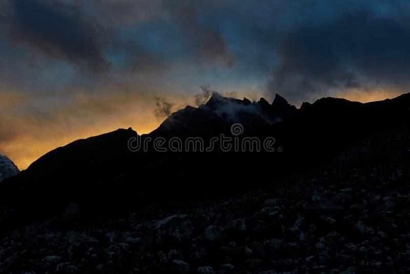 La montagne de l'Himalaya énorme avec des glaciers au Népal a couvert par des nuages avant le lever de soleil photos stock