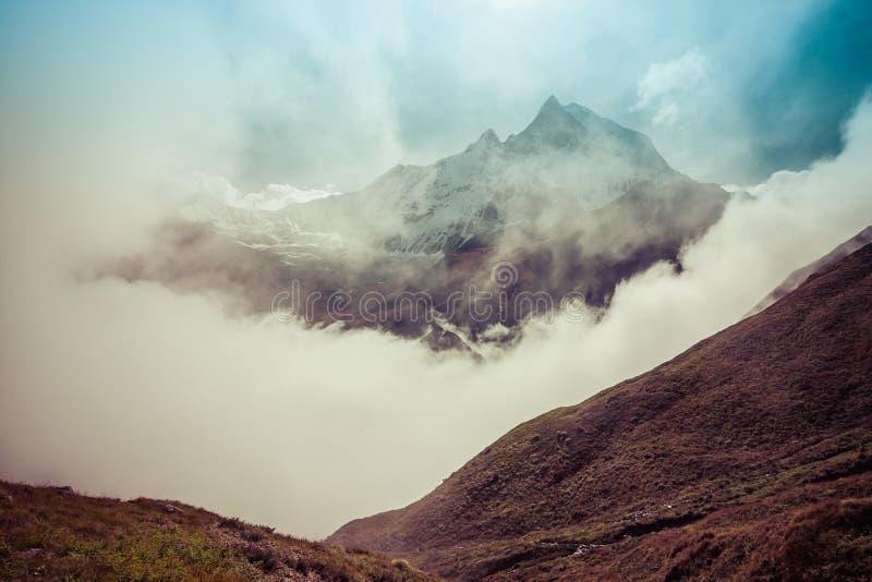 La montagne en queue de poisson sacrée indiquant par de hauts nuages anna photographie stock libre de droits