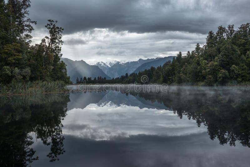 La montagne neigeuse éloignée est reflétée dans l'eau de Matheson de lac photographie stock libre de droits